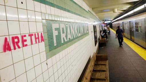 """Aretha"" is spray painted next to a sign at the Franklin Street subway station in the Brooklyn borough of New York"